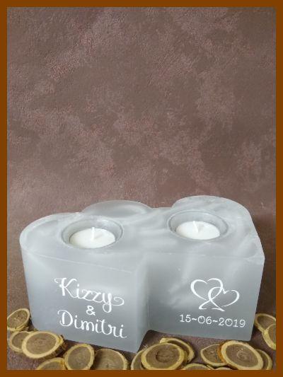 Huwelijkskaars in de vorm van twee hartkaarsen met twee theelichthouders geplaatst op een voetstuk en voorzien van jullie namen en datum